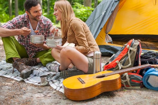 Paar, das ein köstliches abendessen auf dem campingplatz hat