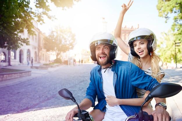 Paar, das ein motorrad fährt, das helme trägt