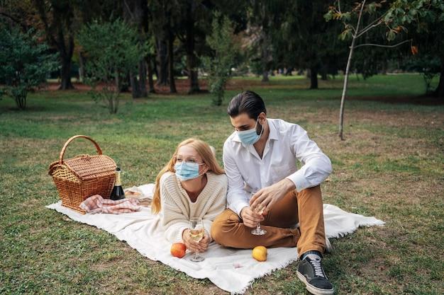 Paar, das ein picknick beim tragen von medizinischen masken hat