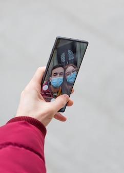 Paar, das ein selfie mit smartphone zusammen nimmt, während es medizinische masken trägt
