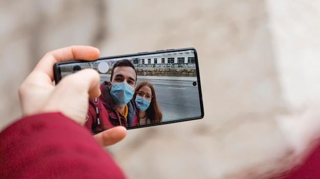 Paar, das ein selfie zusammen mit smartphone nimmt, während es medizinische masken trägt