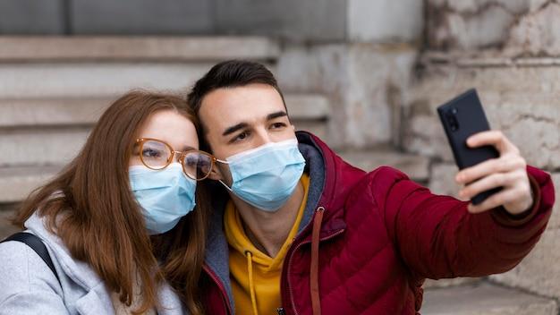 Paar, das ein selfie zusammen nimmt, während es medizinische masken trägt