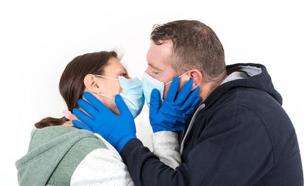 Paar, das ein virusgesichtsmasken-kusskonzept für koronavirus trägt