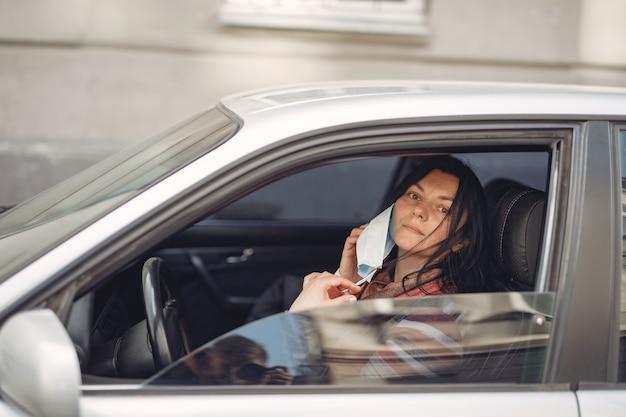 Paar, das eine schutzmaske trägt, die in einem auto sitzt