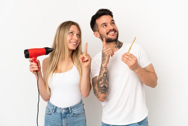 Paar, das einen haartrockner hält und die zähne über isoliertem weißem hintergrund putzt, das mit dem zeigefinger zeigt, eine großartige idee
