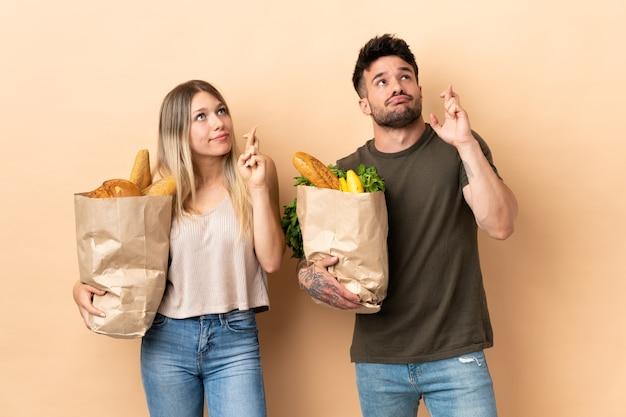 Paar, das einkaufstüten des lebensmittels hält