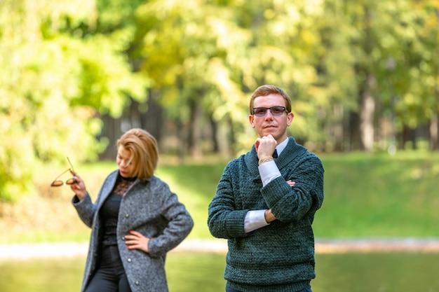 Paar, das ernsthaft draußen in einem park mit einem grünen hintergrund spricht