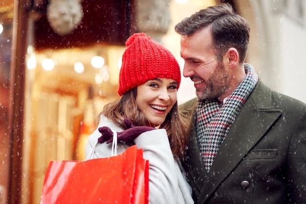 Paar, das etwas geld während des wintereinkaufs ausgibt