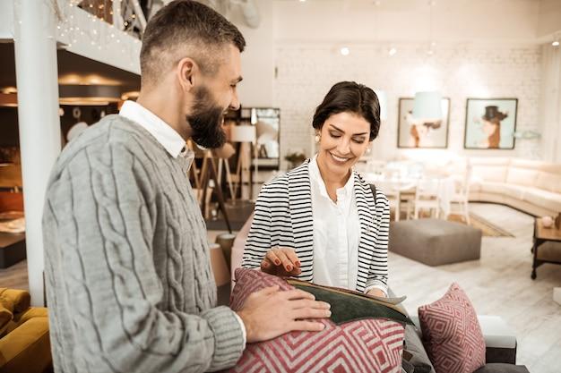 Paar, das farben vergleicht. lächelnde ordentliche frau, die am prozess des hauseinkaufs mit ihrem unterstützenden ehemann interessiert ist