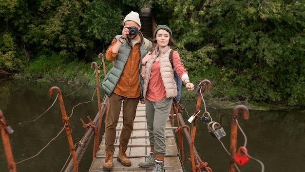 Paar, das fotos auf holzbrücke macht