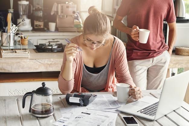 Paar, das gemeinsam das inlandsbudget verwaltet. junge frau in gläsern, die stift halten, während sie berechnungen unter verwendung des taschenrechners und des laptops machen