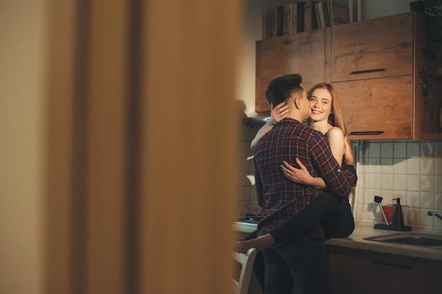 Paar, das gemeinsam freude in der küche an einem warmen sommermorgen hat