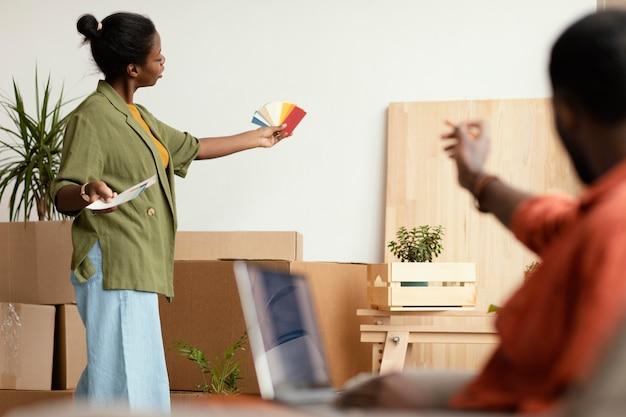 Paar, das gemeinsam pläne für die renovierung des hauses mit laptop und farbpalette macht