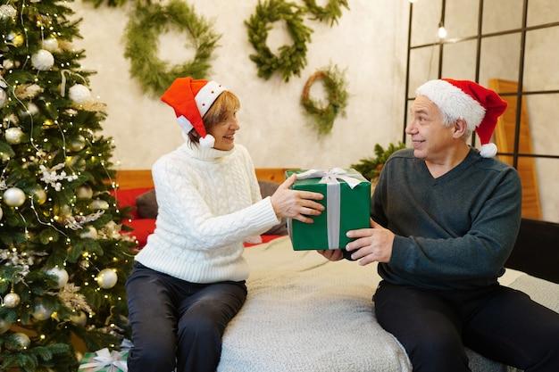 Paar, das geschenk nahe weihnachtsbaum zu hause hält