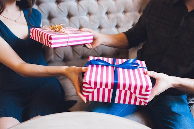 Paar, das geschenke für einander gibt.