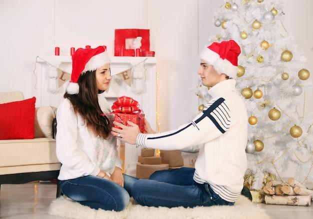 Paar, das geschenke in der weihnachtsnacht austauscht