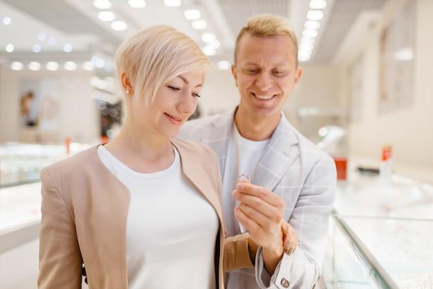 Paar, das golddekoration im juweliergeschäft kauft