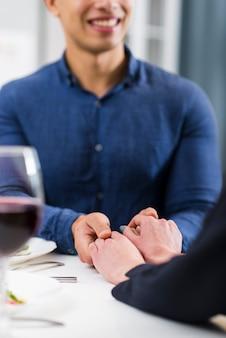 Paar, das hände auf tisch hält
