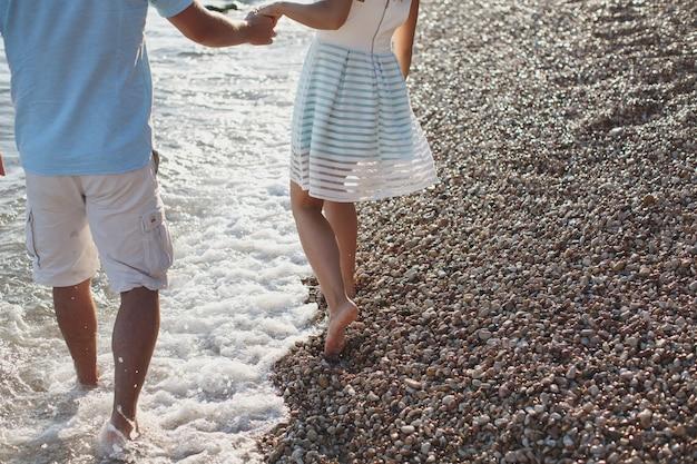 Paar, das hände hält, die auf den kieselsteinen nahe dem meer gehen