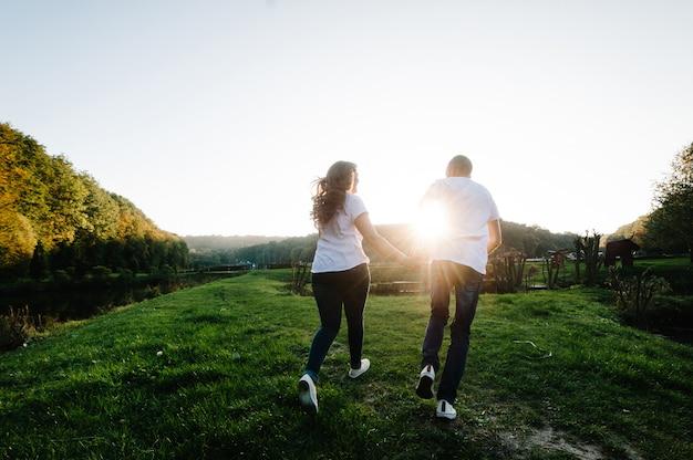 Paar, das hände hält, die weggehen. porträt eines romantischen jungen mannes und einer frau, die in der natur verliebt sind. ehemann und ehefrau rennen durch das feld und halten hände über sonnenuntergang.