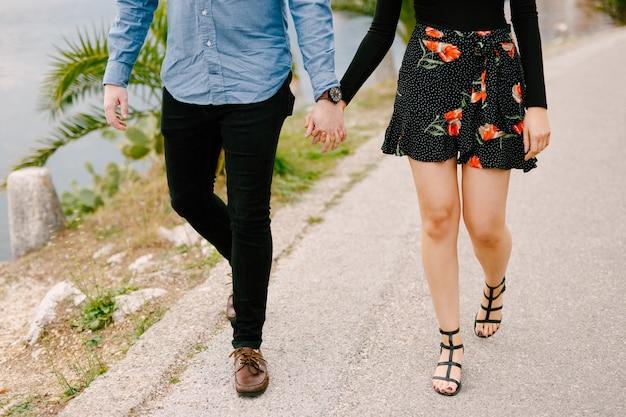 Paar, das hände hält, geht die straße nah oben entlang