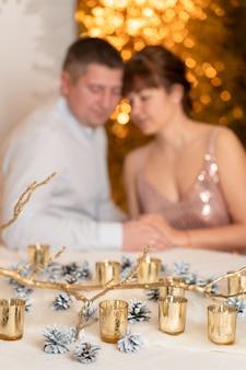 Paar, das hände mit weihnachtsdekorationen auf tisch hält