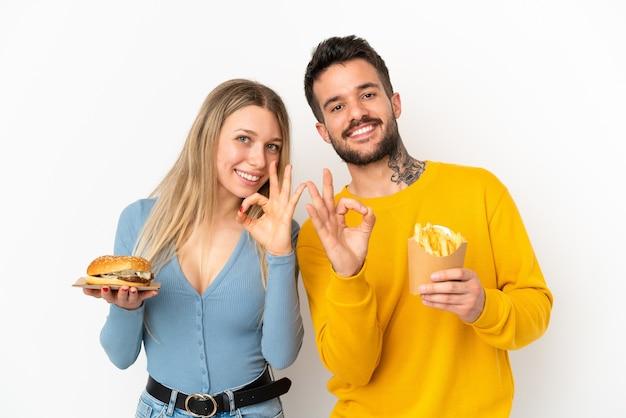 Paar, das hamburger und gebratene pommes über isoliertem weißem hintergrund hält, das ein ok-zeichen mit den fingern zeigt