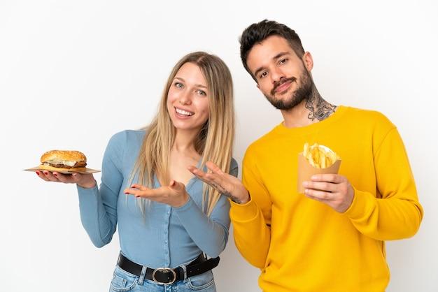 Paar, das hamburger und gebratene pommes über isoliertem weißem hintergrund hält und die hände zur seite ausstreckt, um zum kommen einzuladen?