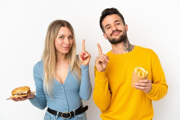 Paar, das hamburger und gebratene pommes über isoliertem weißem hintergrund hält und einen finger im zeichen des besten zeigt und hebt