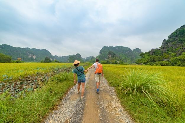 Paar, das hand auf landstraße unter reisfeldern geht. mann mit rucksack und frau mit vietnamesischem hut, der spaß hat, zusammen im urlaub zu reisen.