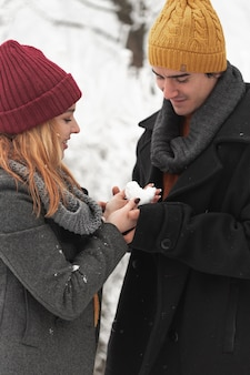 Paar, das herzform aus schnee betrachtet