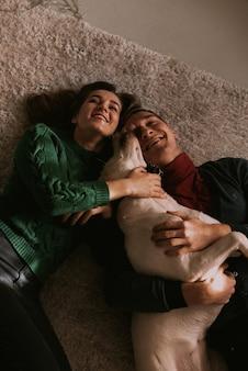 Paar, das hund zu hause umarmt