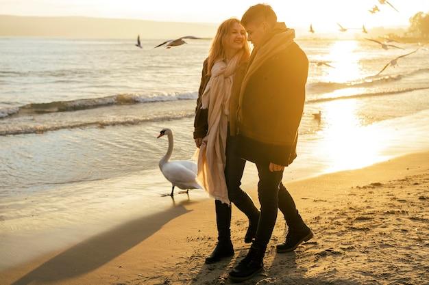 Paar, das im winter am strand spazieren geht