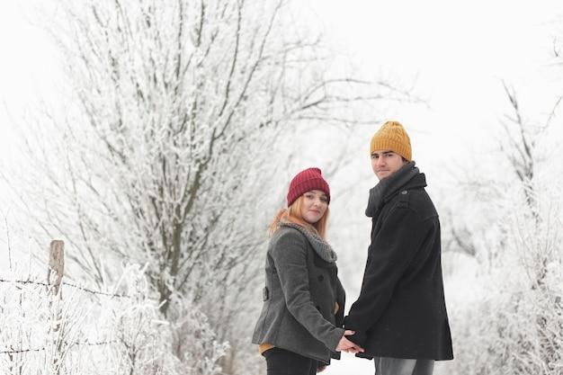 Paar, das im winter im freien geht und hinter mittleren schuss schaut