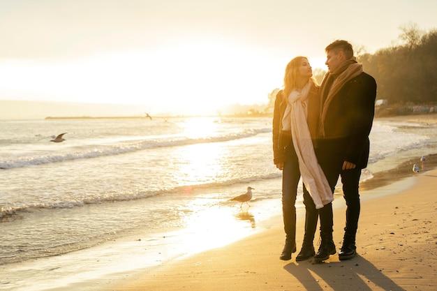 Paar, das im winter zusammen am strand spazieren geht