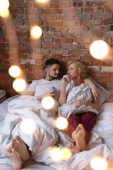 Paar, das im zwillingspyjama auf dem bett liegt und spricht