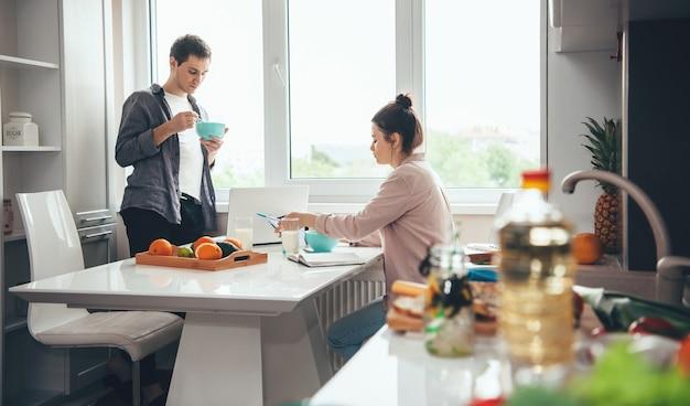 Paar, das in der küche isst, während es online mit einem laptop und einigen büchern arbeitet