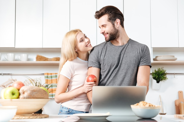 Paar, das in der küche mit laptop kocht