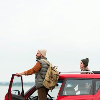 Paar, das in der natur aus dem auto steigt