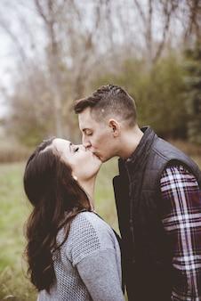 Paar, das in einem garten küsst, der durch grün umgeben ist