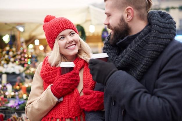 Paar, das kaffee auf weihnachtsmarkt trinkt