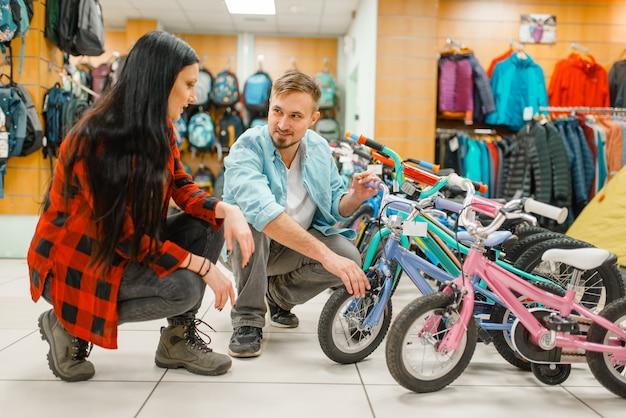 Paar, das kinderfahrrad wählt, einkaufen im sportgeschäft. extremer lebensstil der sommersaison, aktives freizeitgeschäft, kunden, die fahrrad für familienreiten kaufen