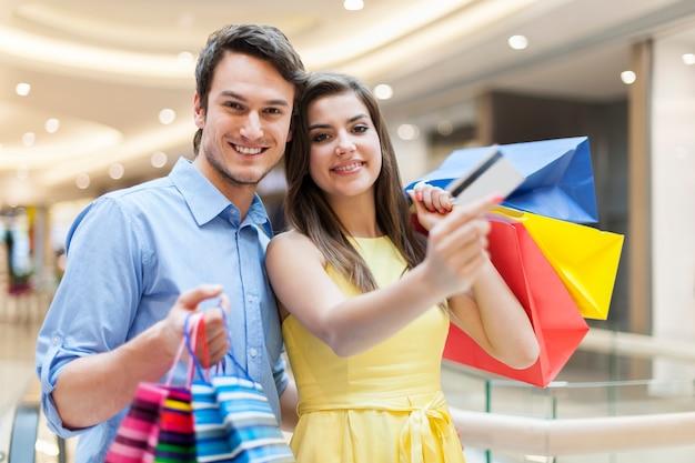 Paar, das kreditkarte im einkaufszentrum zeigt