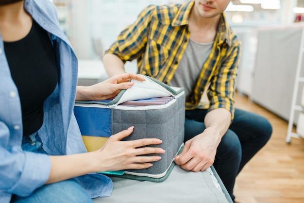 Paar, das matratzenkern für sein bett im ausstellungsraum des möbelhauses wählt.
