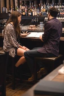 Paar, das menü am bartheke betrachtet