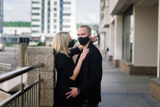 Paar, das modische schutzmasken trägt und in der leeren straße der stadt während der quarantäne geht