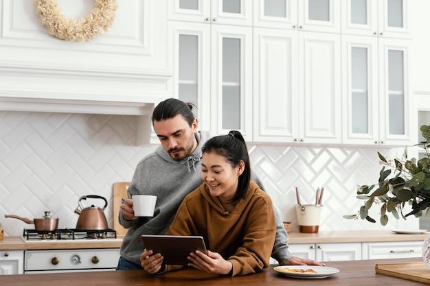 Paar, das morgenmahlzeit in der küche nimmt und eine tablette verwendet