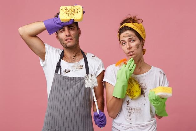 Paar, das müde ist, das haus zu putzen