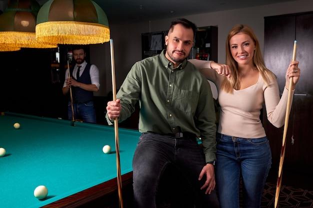 Paar, das nahe dem billardtisch des pools steht, schaut auf kamera, die nach gutem spiel posiert und lächelt. freizeit