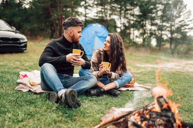 Paar, das nahe lagerfeuer sitzt und heißen tee trinkt